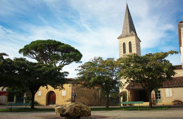 Place du village de Roques avec l'église et la fontaine